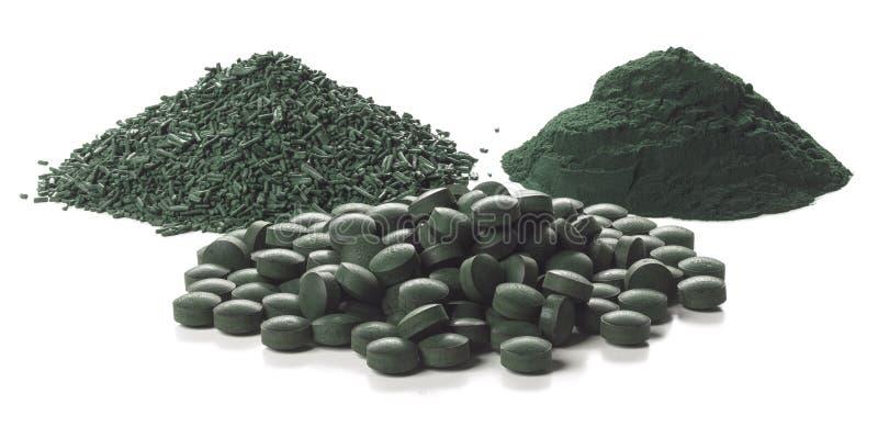 Escamas, tabletas y polvo de Spirulina sobre el fondo blanco foto de archivo libre de regalías