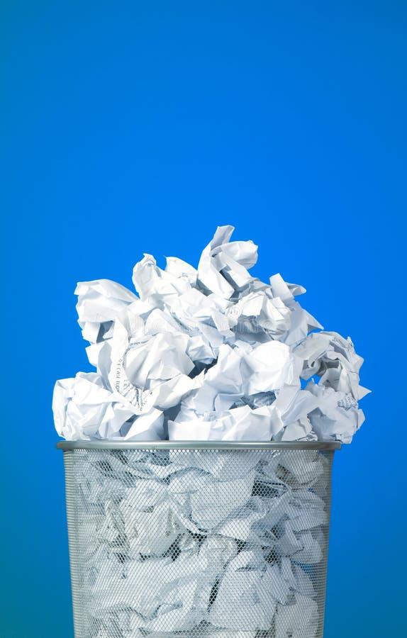 Escaninho de lixo com desperdício do papel de encontro ao fundo fotografia de stock royalty free
