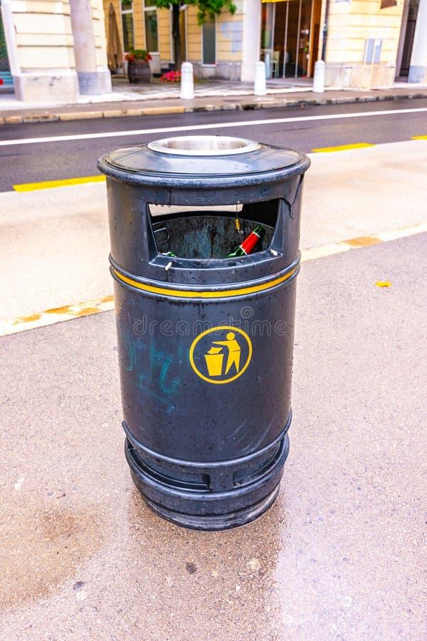 Escaninho de lixo com lixo para dentro na rua da cidade Reciclagem preta na estrada fotografia de stock