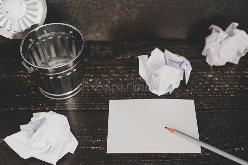 Escaninho de lixo no ajuste da mesa com bloco de notas vazio e as bolas de papel scrunched fotos de stock