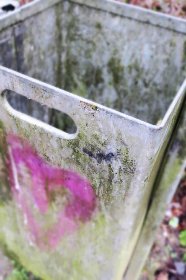 Escaninho de lixo sujo do metal com coração cor-de-rosa fotos de stock