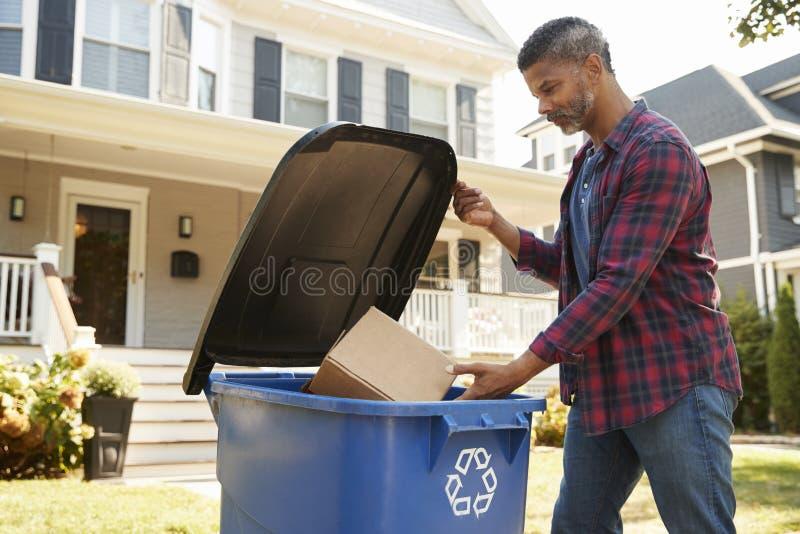 Escaninho de reciclagem de enchimento do homem na rua suburbana imagens de stock