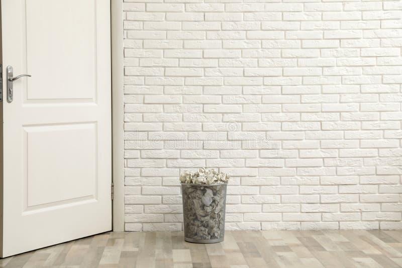 Escaninho do metal com papel amarrotado no assoalho contra a parede de tijolo imagens de stock royalty free