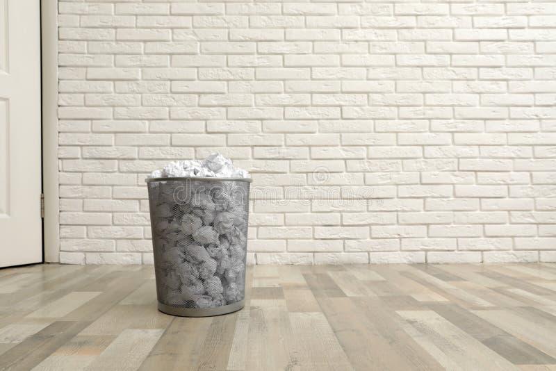 Escaninho do metal com papel amarrotado no assoalho contra a parede de tijolo fotos de stock royalty free