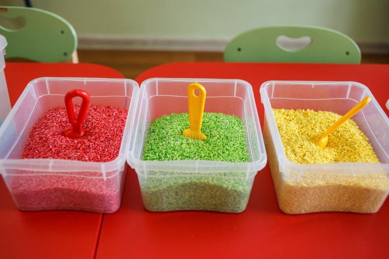 Escaninho sensorial para crianças com arroz colorido na tabela vermelha foto de stock royalty free