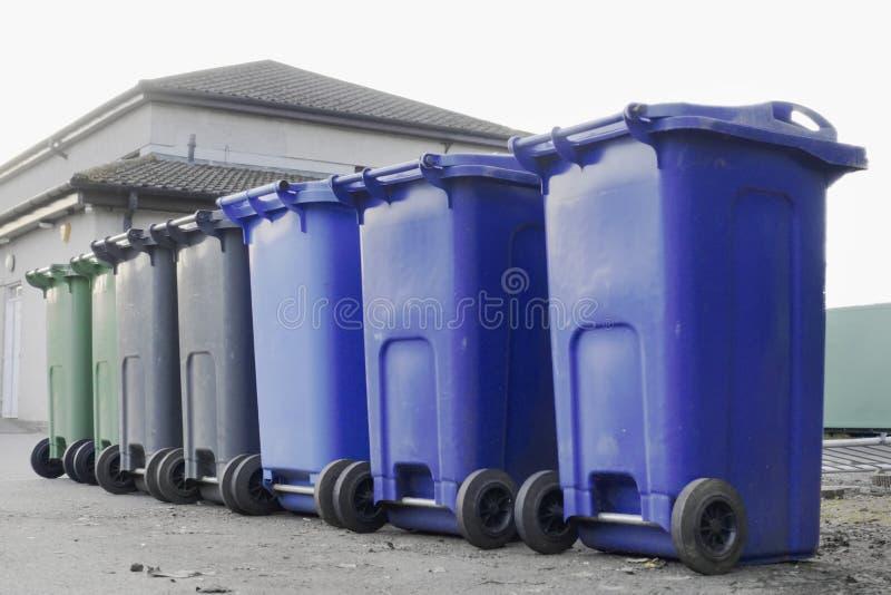 Escaninhos coloridos pretos verdes azuis do wheelie em seguido na rua com os números da casa impressos em homens de espera do esc imagem de stock