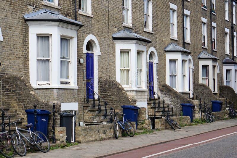 Escaninhos de reciclagem e bicicletas, pista da bicicleta, rua residencial, Cambridge, Inglaterra imagem de stock