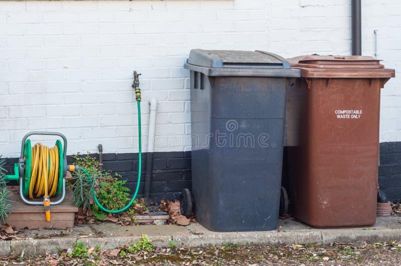 Escaninhos de reciclagem plásticos do agregado familiar contra uma parede foto de stock