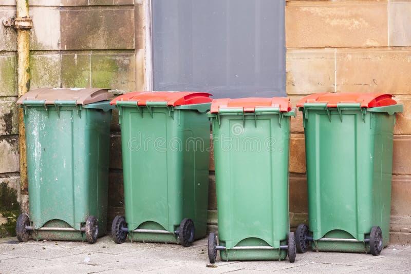 Escaninhos verdes do wheelie na fileira Reino Unido fotografia de stock
