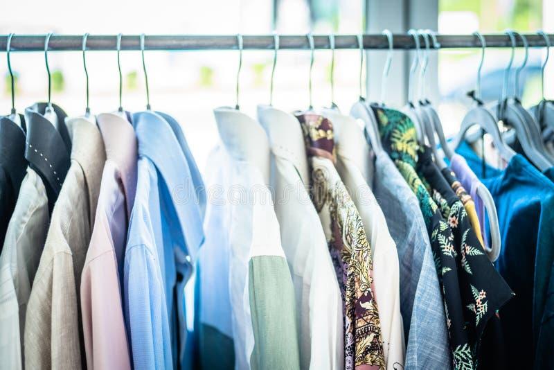 Escaparate de la ropa de verano Géneros de punto blancos y grises del tono que cuelgan en un estante de la capa Foco selectivo, h fotografía de archivo libre de regalías