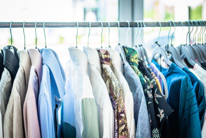 Escaparate de la ropa de verano Géneros de punto blancos y grises del tono que cuelgan en un estante de la capa Foco selectivo, h fotografía de archivo