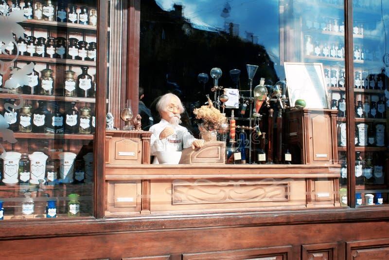 Escaparate de una farmacia del vintage con las pociones, frascos, botellas y farmac?utico de la marioneta, situado en la ciudad d fotos de archivo libres de regalías