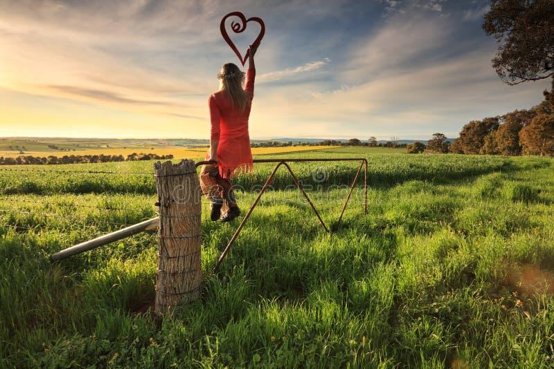 Escape ao país - fêmea na cerca com coração do amor no morni imagem de stock