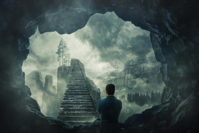 Escape from the dark cave. Surreal view as a man escape from a dark cave stand in front of a mystic stairway crossing the misty abyss going up to unknown royalty free stock photo