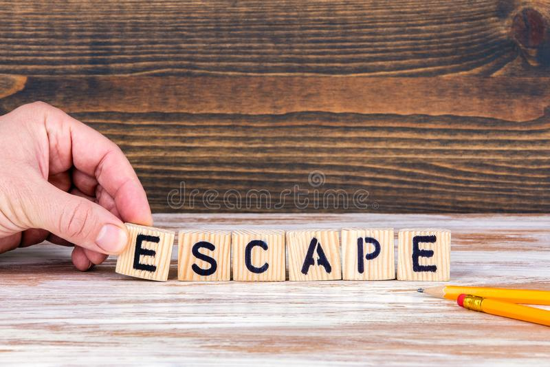Escape. Wooden letters on the office desk. Informative and communication background stock photography