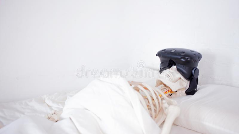 Escapism and horrors of virtual reality, the concept. A human skeleton in a VR helmet, lying in a white room on a bed royalty free stock photo
