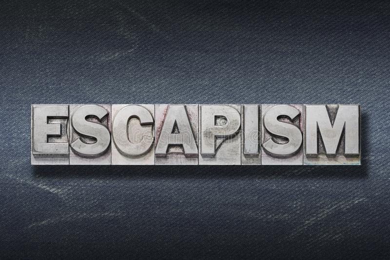 Escapism word den. Escapism word made from metallic letterpress on dark jeans background stock images