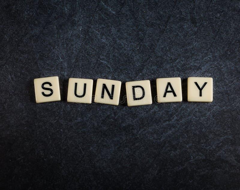 Escarafunchar telhas da letra no fundo preto da ardósia que soletra domingo fotografia de stock