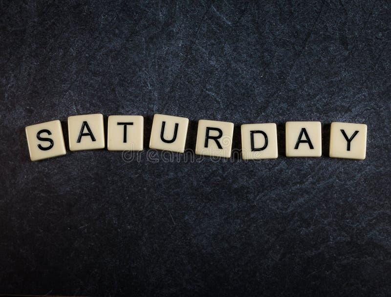 Escarafunchar telhas da letra no fundo preto da ardósia que soletra sábado fotos de stock