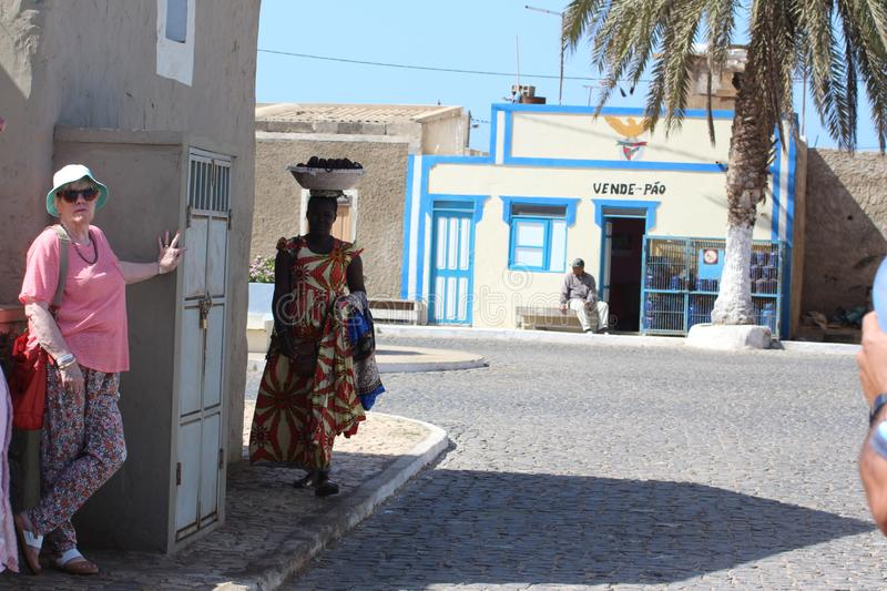This is Escargos, Sal, Cape Verde. Locals, tourists mill around and women here carry their wares on their head with a flat pad holding the bowel steady royalty free stock images