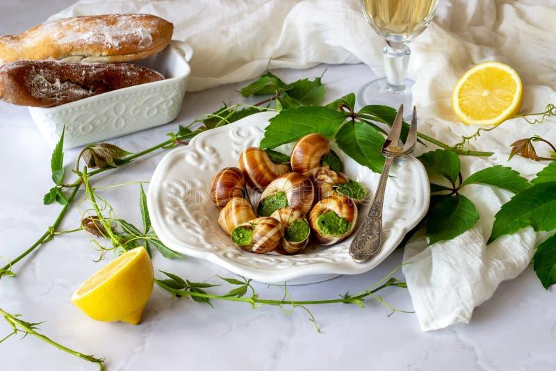 Escargot de Bourguignonne avec le citron Fond de marbre Cuisine fran?aise images libres de droits