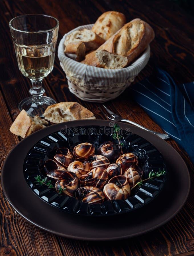 Escargot z szkłem biały wino i świeży baguette fotografia stock