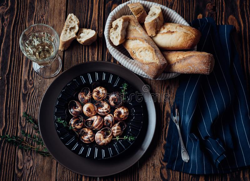 Escargot z szkłem biały wino i świeży baguette obraz royalty free