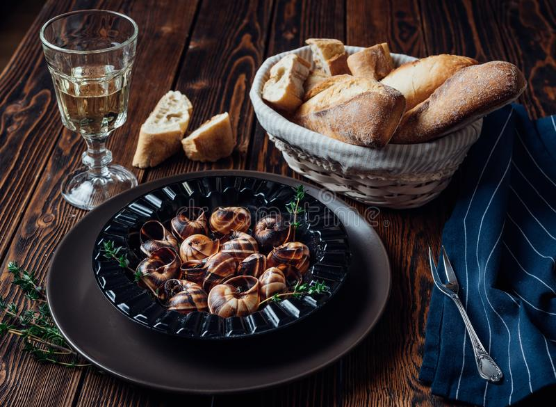 Escargot z szkłem biały wino i świeży baguette obraz stock