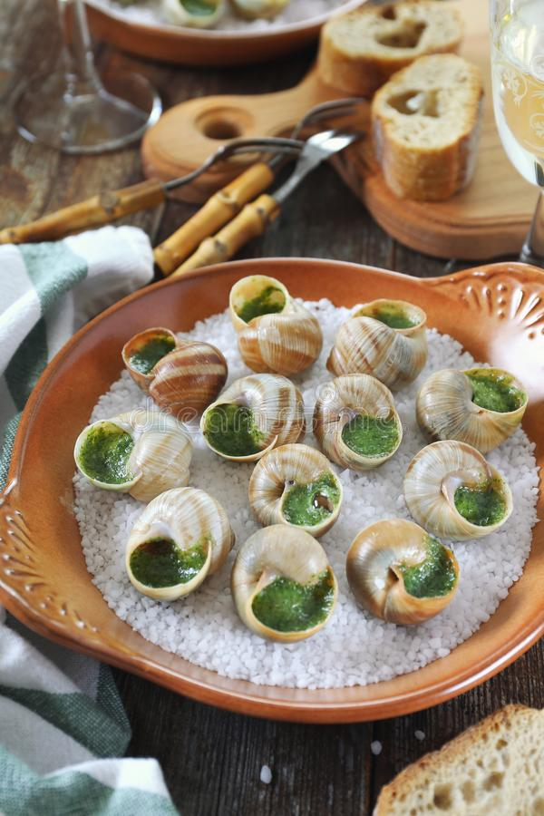 Escargots, French cuisine: snails sauce Burgundy and white wine. Escargots, traditional French cuisine: snails sauce Burgundy and glass of white wine royalty free stock photos