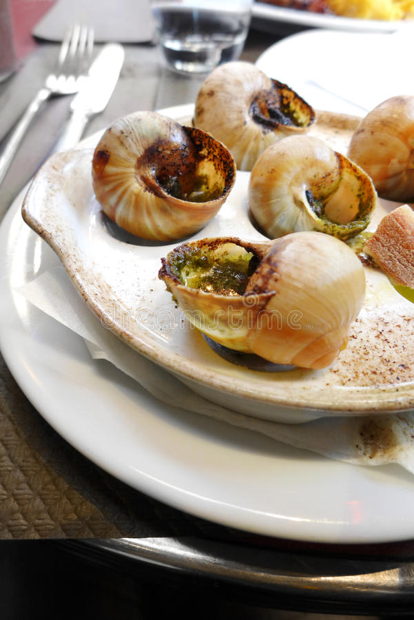 Escargots snails in french restaurant cafe. An indoor restaurant food photograph showing a dish of snails or escargot baked with herbs and butter. A very popular stock photos