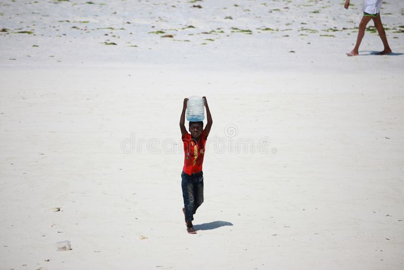 Escasez del agua en el concepto de África Un niño pequeño lleva el agua en su cabeza en un envase de plástico Isla de Zanzíbar, T imagen de archivo