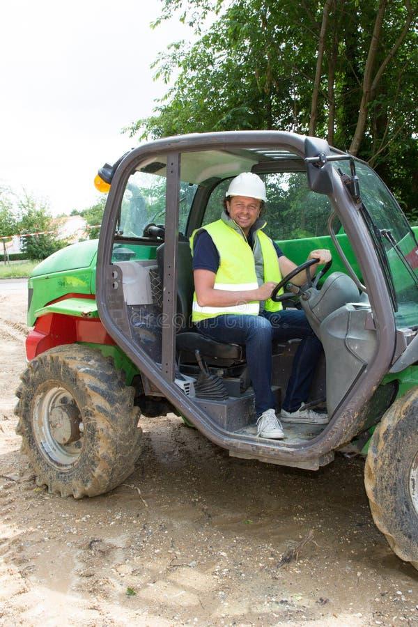 Escavação da máquina escavadora do motorista e terra movente no canteiro de obras foto de stock royalty free