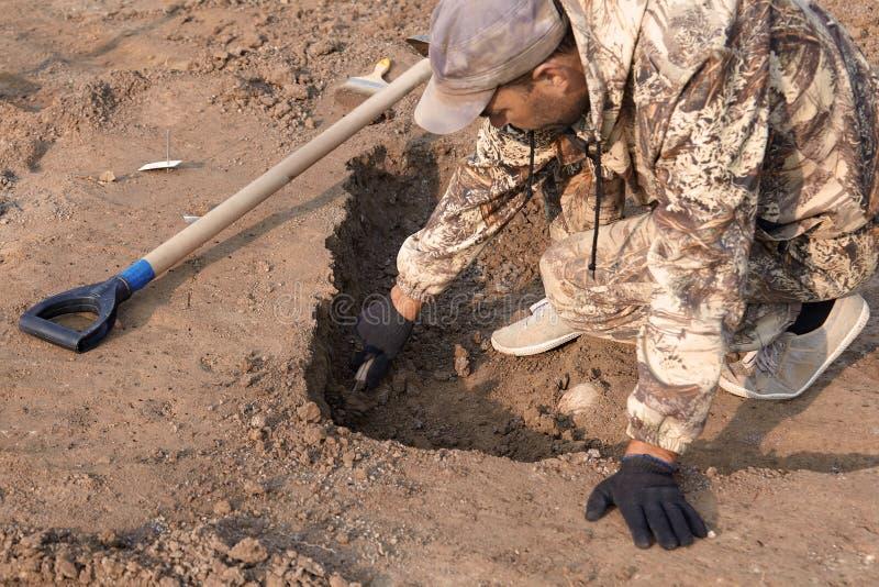 Escavações Archaeological O arqueólogo em um processo do escavador As mãos com pesquisa de condução sobre a terra, pá da faca são foto de stock