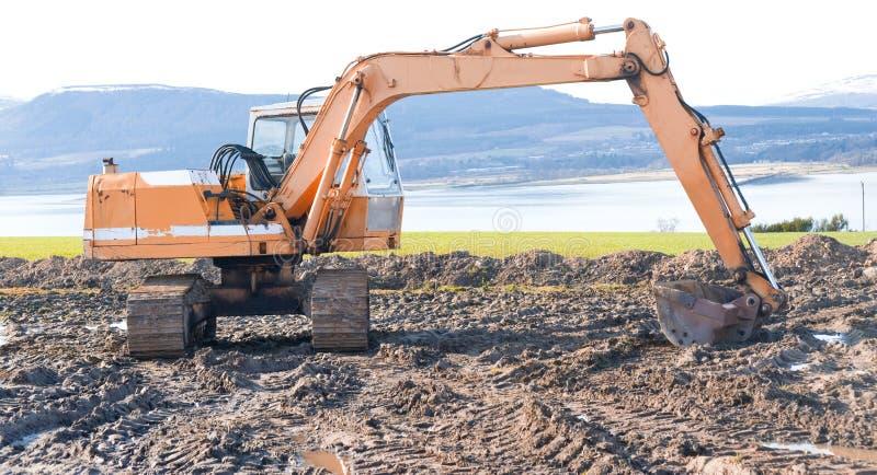 Escavador na operação na costa. fotografia de stock royalty free