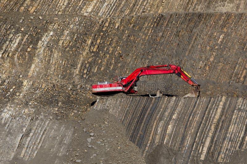 Escavador vermelho no pedra-poço foto de stock royalty free