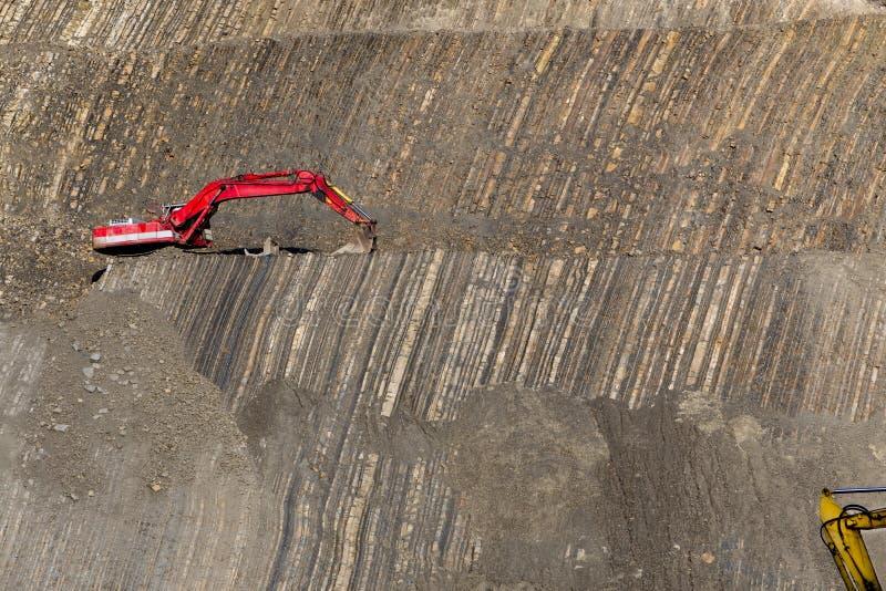 Escavador vermelho no pedra-poço fotografia de stock