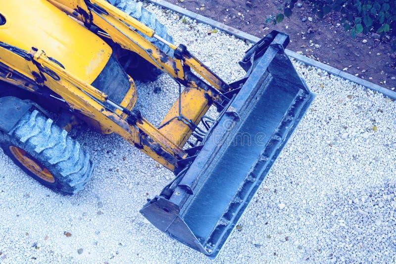 Escavadora amarela, cascalho de carregamento para a construção de estradas imagens de stock