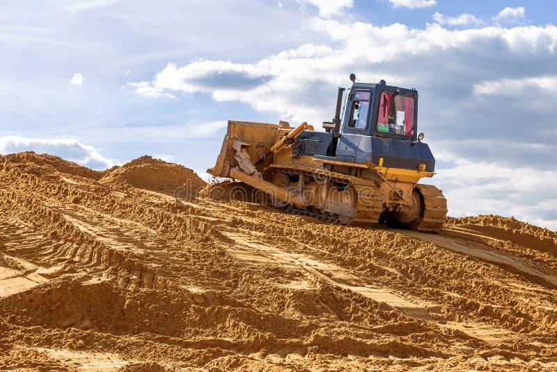 A escavadora conduz terraplenagens no canteiro de obras imagem de stock