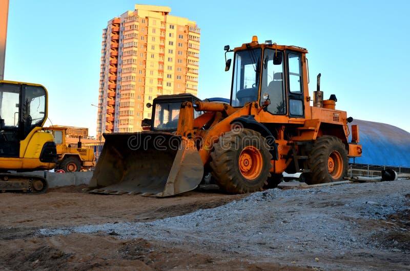 Escavadora diesel do carregador da roda com cubeta em um canteiro de obras contra uma construção residencial imagem de stock royalty free