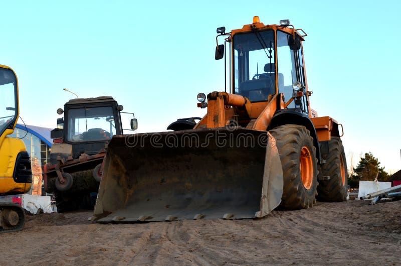 Escavadora diesel do carregador da roda com cubeta em um canteiro de obras contra uma constru??o residencial imagens de stock royalty free