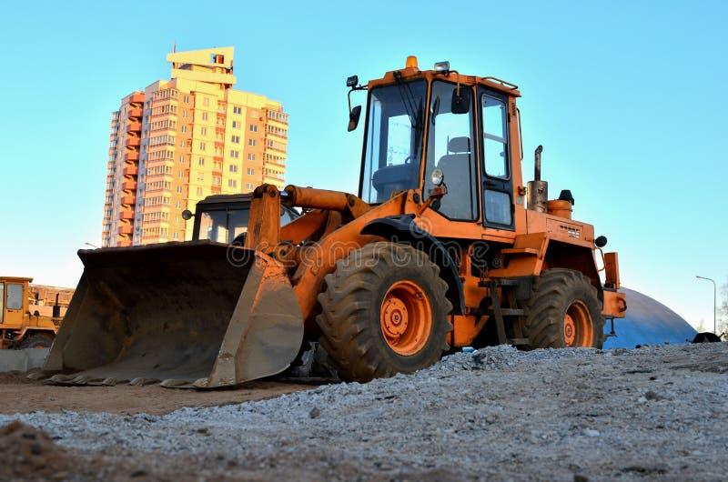 Escavadora diesel do carregador da roda com cubeta em um canteiro de obras contra uma constru??o residencial foto de stock royalty free