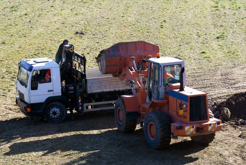 Escavadora e caminhão no trabalho imagens de stock
