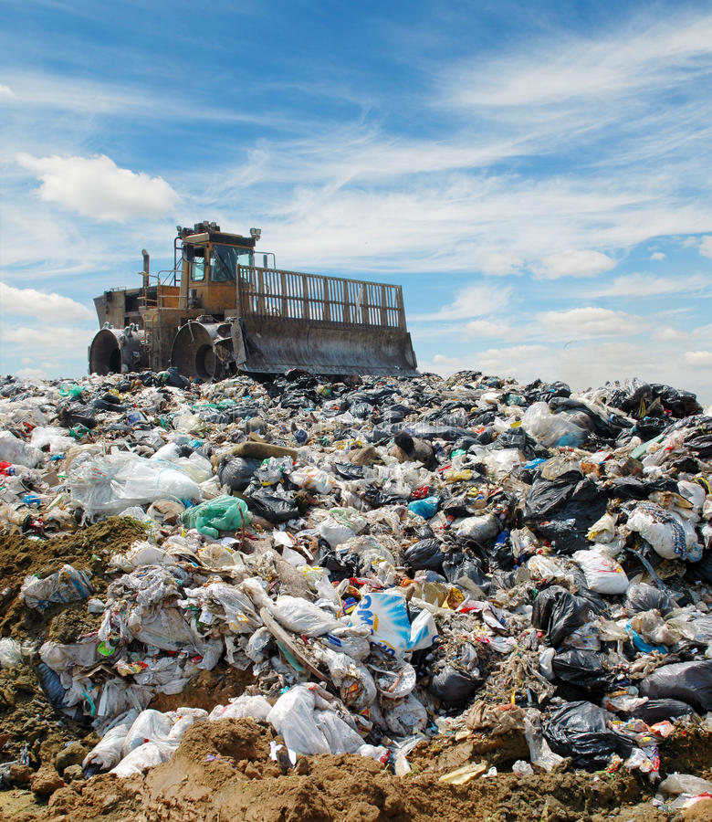A escavadora em uma descarga de lixo fotos de stock royalty free