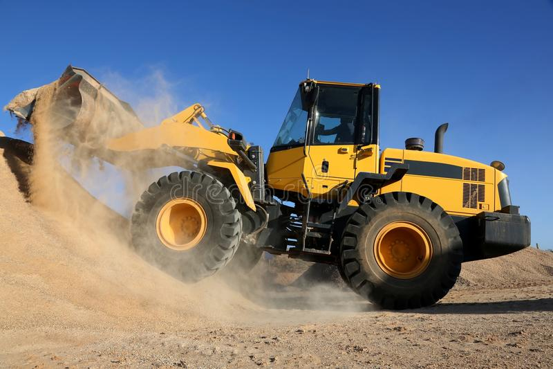 Escavadora que trabalha com areia imagens de stock royalty free
