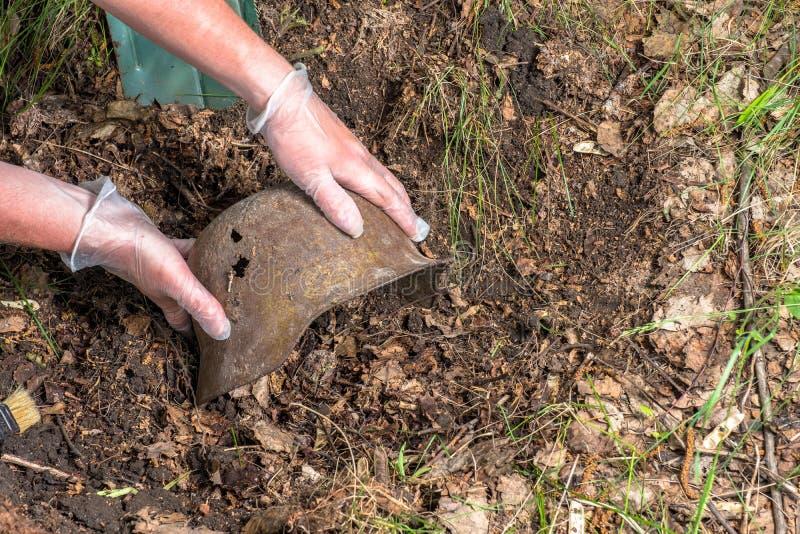 Escavando na floresta o capacete alemão M35 imitation Recuperação WW2 Rússia fotos de stock