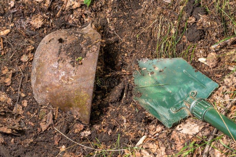 Escavando na floresta o capacete alemão M35 imitation Recuperação WW2 Rússia fotos de stock royalty free