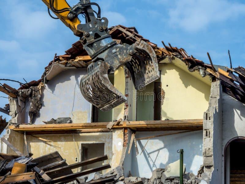 Escavatore che demolisce una casa fotografia stock libera da diritti