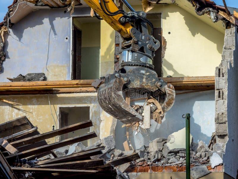 Escavatore che demolisce una casa immagine stock