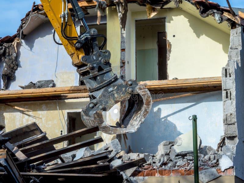 Escavatore che demolisce una casa fotografia stock
