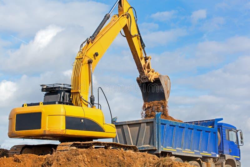 Escavatore che scarica sabbia nell'autocarro a cassone immagine stock libera da diritti